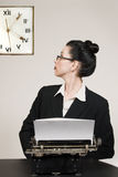 Long Day. Retro business woman with vintage typewriter looking at wall clock royalty free stock photo