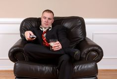 Long day at Work. A man with a television remote and drink in hand relaxing, after a long day at work stock image