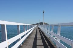 Long deserted jetty into Auckland Harbour. Long jetty with white wooden rails extends into Auckland Harbour Stock Images