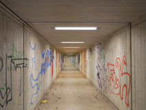 Long deserted underpass or subway with graffiti. Long deserted underpass, tunnel, passageway or subway with scrawled spray painted graffiti on the walls and a Royalty Free Stock Photos