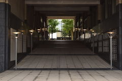 Long dimly lit hallway leading to the street. Lamps on the side of the path Stock Photos