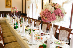 Long dinner table decorated with pink flowers in high vases Royalty Free Stock Images