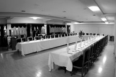 Long dinner table setup. A black and white picture of a long u shaped dinner table table setup in a hall stock photography