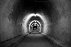 A long dirty tunnel photographed in black and white. The entrance to a long tunnel. In order to better capture the atmosphere, colors were omitted in this image royalty free stock photo