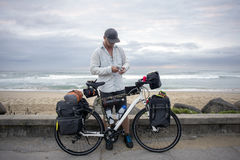 Long Distance Cyclist with Bicycle by Ocean Stock Photos