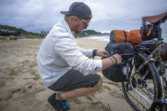 Long Distance Cyclist Prepares Panniers while on Beach Stock Image