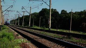 Long distance trains. Summer. Sunny weather. Railroad tracks in the woods. The passenger train travels fast stock video footage