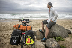 Long Distnace Cyclist with Bicycle on Beach. A long distance cyclists sits on a rock by the beach viewing the ocean with his packed bicycle standing next to him stock images