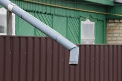 Long drain gris en métal au mur brun de la barrière images stock