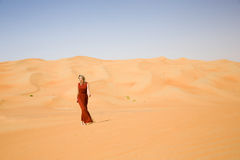 Long dressed woman walks in desert Stock Images