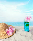 Long drink on the beach. Blue longdrink on the beach with a sunhat and sea shells Royalty Free Stock Image