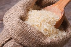 Long dry rice on wooden spoon macro in the sack Stock Photo