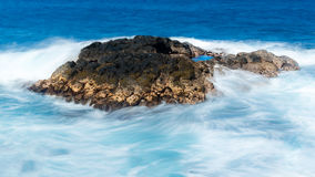 Long duration shot of waves flowing over lava rock royalty free stock photos