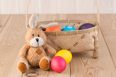 Long-eared Easter bunny and basket. With Easter eggs Stock Photos