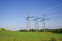 Long electric lines, towers and high voltage lines in a field in summer.  stock photo
