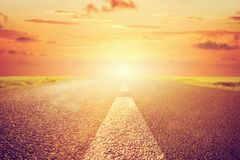 Long empty asphalt road towards sunset sun. Royalty Free Stock Photo
