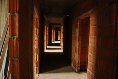 Long empty corridor between brick walls. With periodic openings allowing in daylight receding into the distance royalty free stock photo