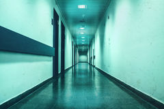 Long empty corridor washed in bluish depressive light Royalty Free Stock Photography