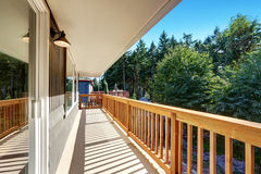 Long empty deck with wooden railings and backyard view. Royalty Free Stock Photography