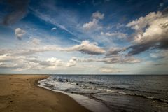 Long empty sand beach on Hel peninsula in Poland with dramatic, cloudy blue sky.  stock image