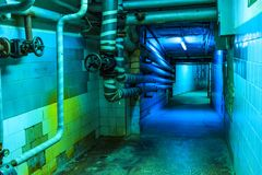 long empty tunnel with pipes and utilities on ceiling, blue neon lights royalty free stock photos