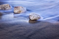 Long exposed wave against stones Royalty Free Stock Image