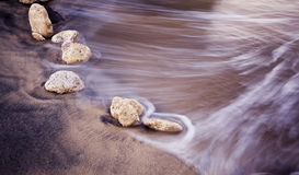 Long exposed wave against stones Royalty Free Stock Images