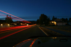 Long Exposure. A long streak of red lights is left as the vehicle passes and leaves a trail Royalty Free Stock Photography