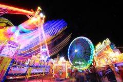 Long exposure of amusement park. Carousel and ferris wheel blurry movement at night with long exposure Royalty Free Stock Image
