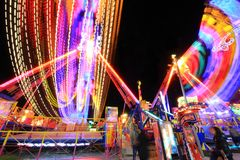 Long exposure of amusement park. Carousel and ferris wheel blurry movement at night with long exposure Royalty Free Stock Photography
