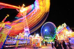 Long exposure of amusement park. Carousel and ferris wheel blurry movement at night with long exposure Royalty Free Stock Photo