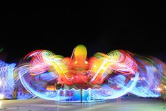 Long exposure of amusement park. Carousel and ferris wheel blurry movement at night with long exposure Stock Photo