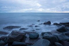 A long exposure of beach water on a rocky ocean coastline royalty free stock image