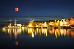 Long exposure of Bergen during the night at harbor with parking cruise under full blue moon royalty free stock image
