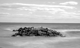 Long exposure black and white shoreline rocks. Long exposure black and white daytime stock photo of rocks off the shoreline of beach in Spring Lake, New Jersey Stock Photography