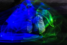 Long exposure blue and green light lines movement over sneakers Royalty Free Stock Photo