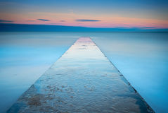 Long Exposure of Blyth Beach Jetty. Minimalistic view of the concrete jetty, reaching out into the North Sea at Blyth in Northumberland, at sunset Royalty Free Stock Image