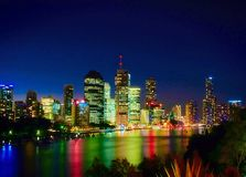 Long exposure of Brisbane City and river at night. Red green yellow blue reflections from the water Royalty Free Stock Photos
