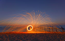 Long exposure of burning steel wool being spun into a sphere on. The coastline before sunset royalty free stock photo