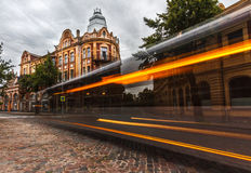 Long-exposure of bus with historical building. Stock Images