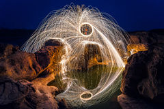 Long exposure capture of Burning steel wool. Being spun before dusk on a grand canyon rock field stock images