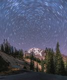 A long exposure captures the star trails around the north star. Over Mount Shasta Stock Photo