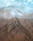 A Long exposure captures the waves and incoming tide on Four Mile Beach. In Davenport California Stock Photography