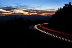 Long Exposure. Of a car streaking through a dark road Stock Photo