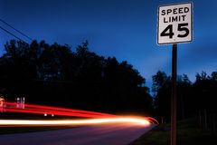 Long exposure of cars passing by a speed limit sign Royalty Free Stock Photos