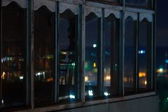 Long exposure cityscape night photo. Balcony with windows let through the lights stock image