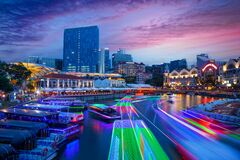 Long exposure of colorful boats moving on Singapore River during sunset blue hour
