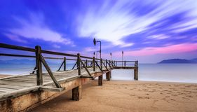 Long exposure of colorful sunrise and wooden pier Stock Photo