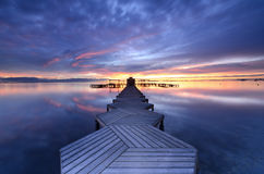 Long Exposure of a colorful sunrise in a zigzag pier placed in Mar Menor, Murcia Stock Photo