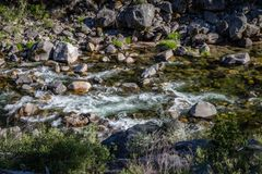 Cool creek flowing from left to right with smooth rocks and deep green water. Long exposure of a cool creek flowing from left to right with smooth rocks and deep royalty free stock photography